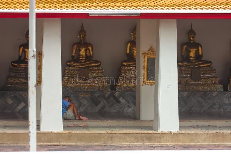 Banguecoque, Tailândia - 29 de abril de 2014 Homem que descansa e que reza na frente das esculturas douradas da Buda em Wat Pho,  imagem de stock
