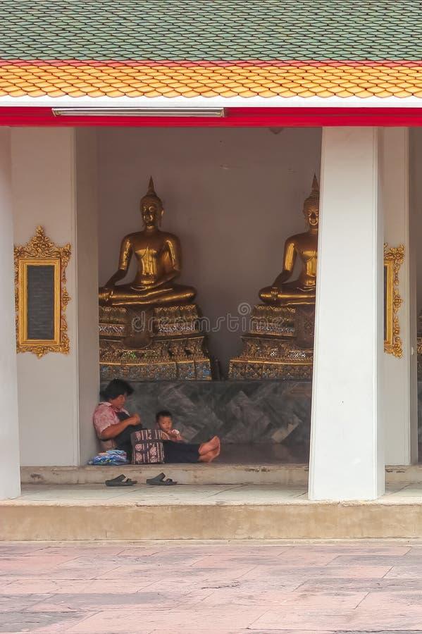 Banguecoque, Tailândia - 29 de abril de 2014 Mãe e filho que sentam-se na frente das esculturas douradas da Buda em Wat Pho, Tail fotografia de stock royalty free