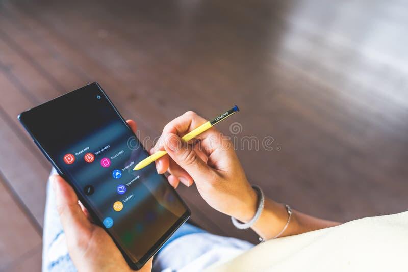 Banguecoque, Tailândia - 28 de agosto de 2018: Mão asiática da mulher usando a pena amarela de S na tela da nota 9 da galáxia de  fotografia de stock