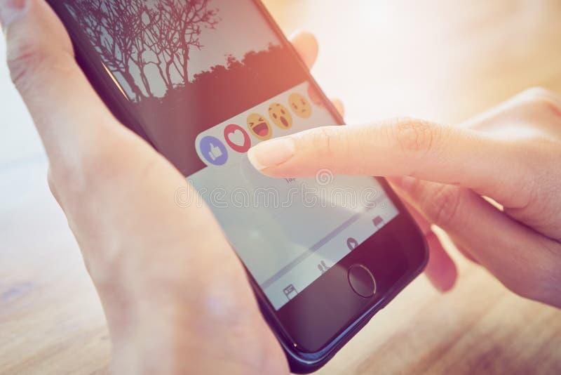 Banguecoque, Tailândia - 2 de janeiro de 2018: a mão está pressionando a tela de Facebook na maçã iphone6, meios sociais está usa fotos de stock royalty free