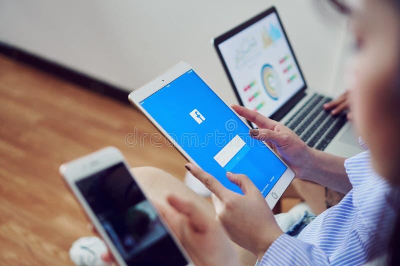 Banguecoque, Tailândia - 31 de janeiro de 2018: a mão está pressionando a tela de Facebook no ipad pro, meio social da maçã imagem de stock royalty free