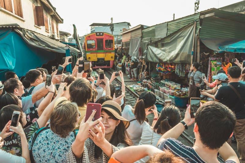 Banguecoque, Tailândia - 27 de janeiro de 2018: Turistas que tomam fotos do trem no mercado da trilha de estrada de ferro de Maek foto de stock royalty free