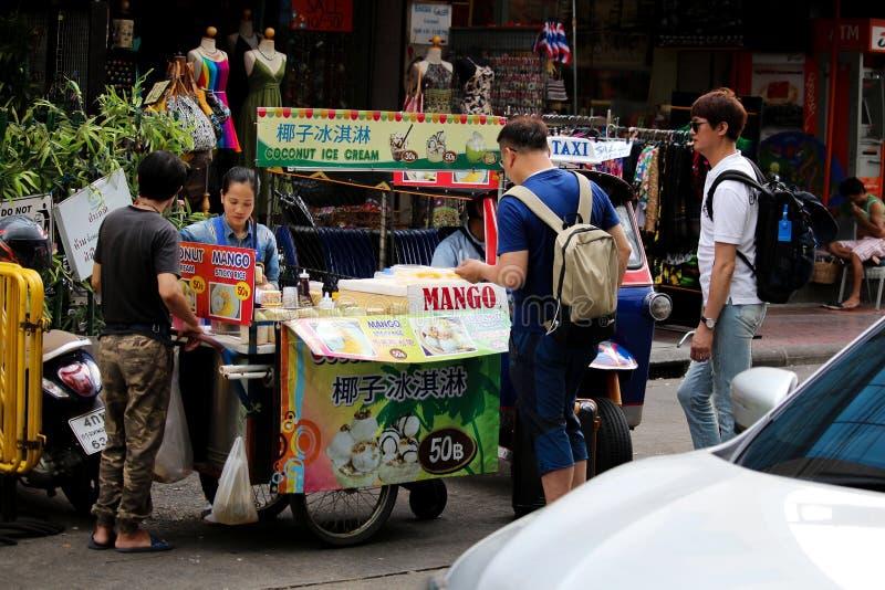 Banguecoque, Tailândia - 3 de junho de 2018: Jovens mulheres e gelado de coco da venda do marido e arroz pegajoso da manga perto  fotos de stock