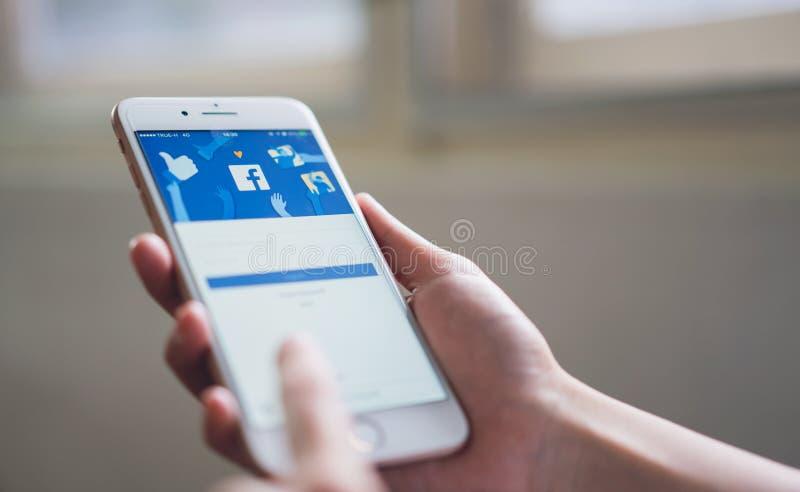 Banguecoque, Tailândia - 5 de novembro de 2018: a mão está pressionando a tela de Facebook no iphone 6 da maçã fotos de stock