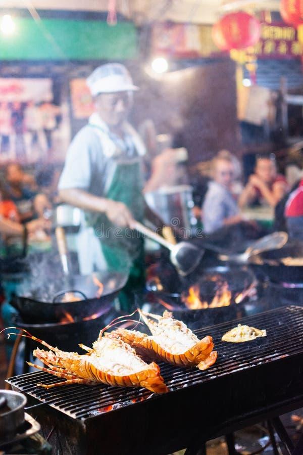 Banguecoque, Tailândia - em março de 2019: homem que cozinha o marisco no restaurante chinês da rua do mercado da noite imagens de stock royalty free