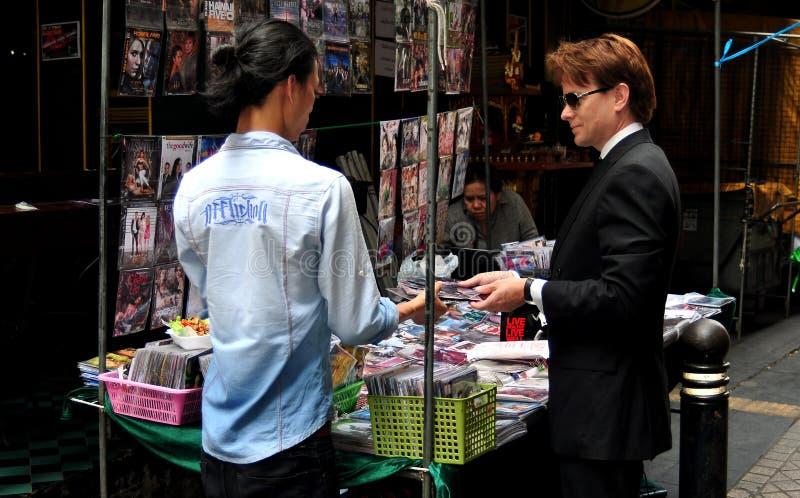 Banguecoque, Tailândia: Homem que compra vídeos de DVD imagens de stock