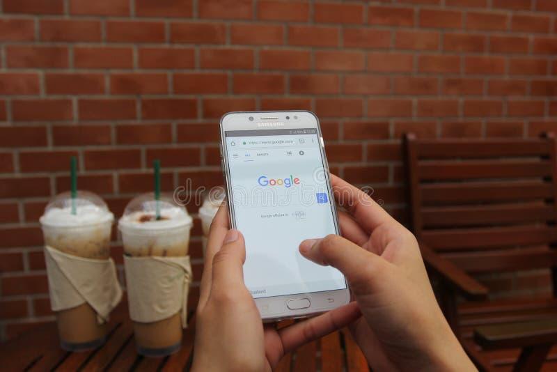 Banguecoque, Tailândia: Jane 13, 2018, mão da mulher usando o sinal de adição da galáxia J7 de Samsung com Home Page da busca de  foto de stock royalty free