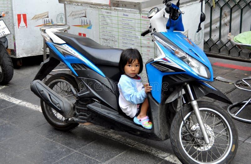 Banguecoque, Tailândia:  Menina tailandesa pequena assentada na motocicleta imagens de stock