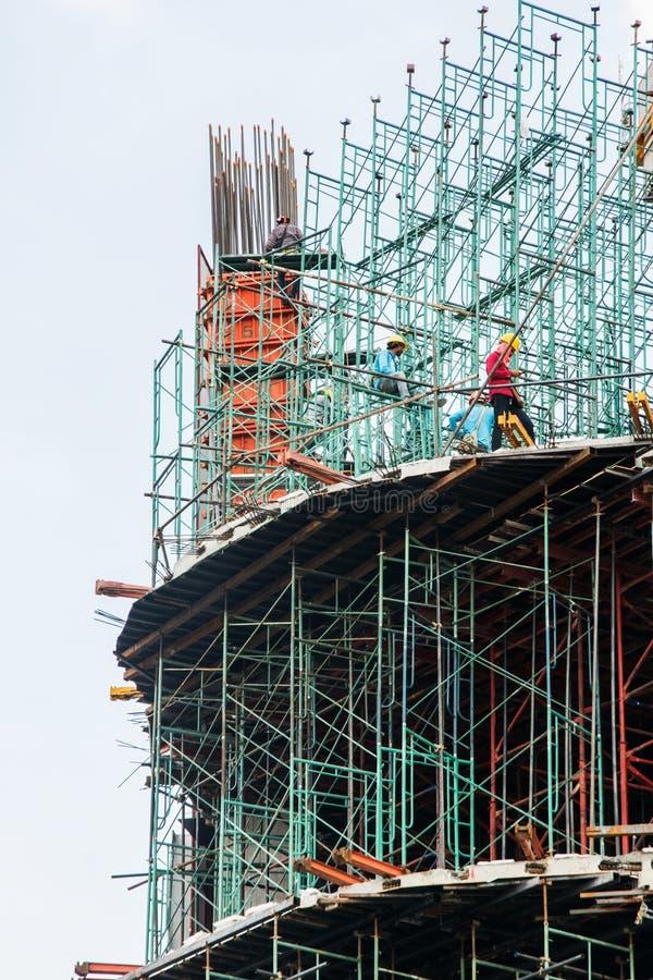 BANGUECOQUE, TAILÂNDIA - 1º DE ABRIL DE 2017: Construtores no andaime no canteiro de obras Construção moderna Multistorey sob o c foto de stock royalty free