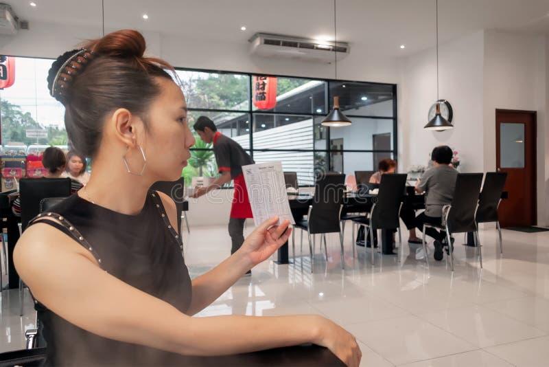 BANGUECOQUE, TAILÂNDIA - 28 DE DEZEMBRO: O cliente não identificado tenta obter sobre o serviço no restaurante do bufete da corre imagem de stock