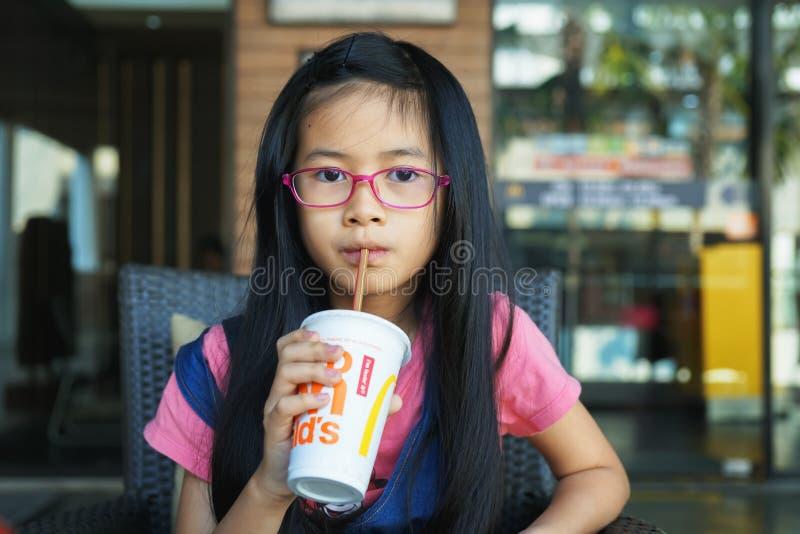 BANGUECOQUE, TAILÂNDIA - 19 DE JANEIRO DE 2019: a menina asiática pequena bebeu a bebida fria da palha na frente do café de McDon imagens de stock