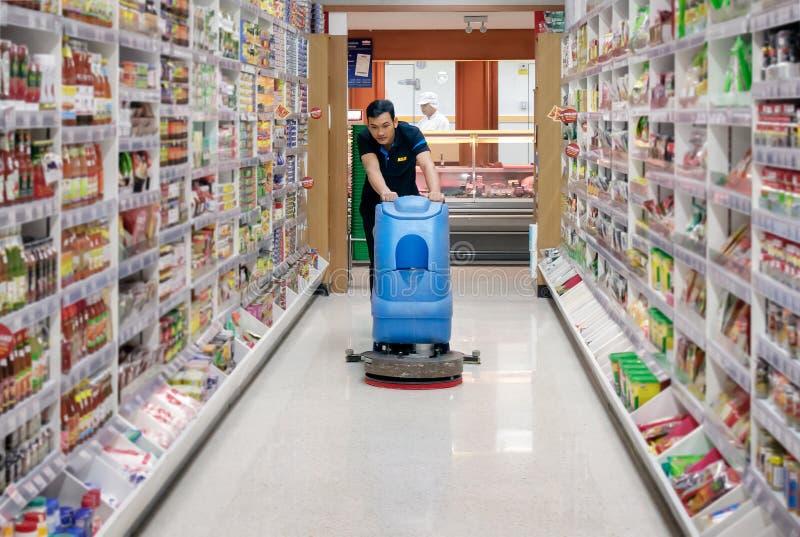 BANGUECOQUE, TAILÂNDIA - 16 DE JUNHO: O empregado anônimo do supermercado de Foodland limpa o assoalho com uma máquina em Banguec fotografia de stock royalty free