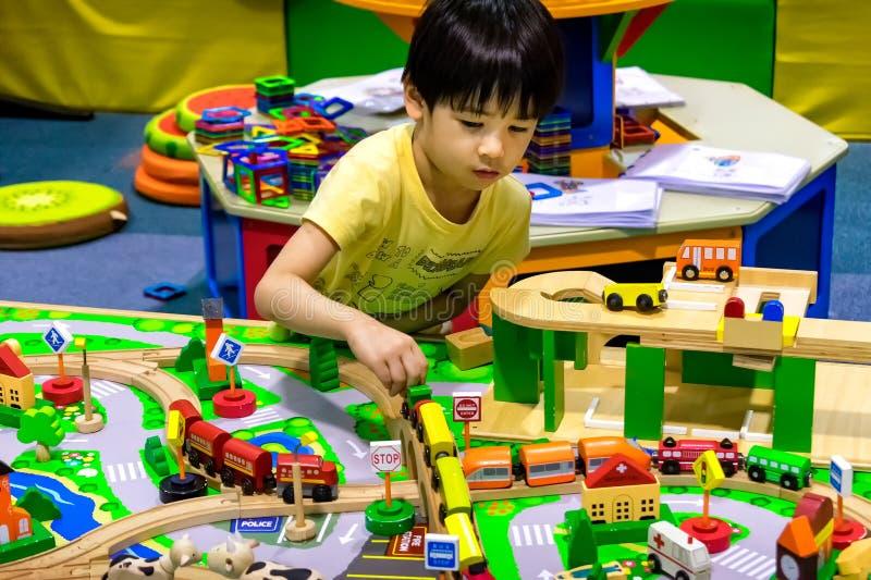 BANGUECOQUE, TAILÂNDIA - 18 DE JUNHO: Um menino joga com trem de madeira ajustou i imagens de stock royalty free