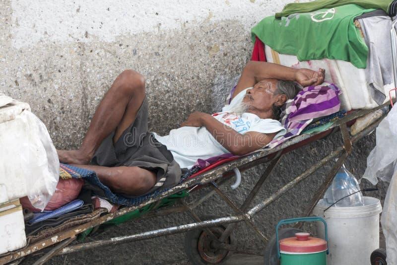 BANGUECOQUE, THAILAND-SEPT 25o: Um homem desabrigado dorme entre seu p imagens de stock