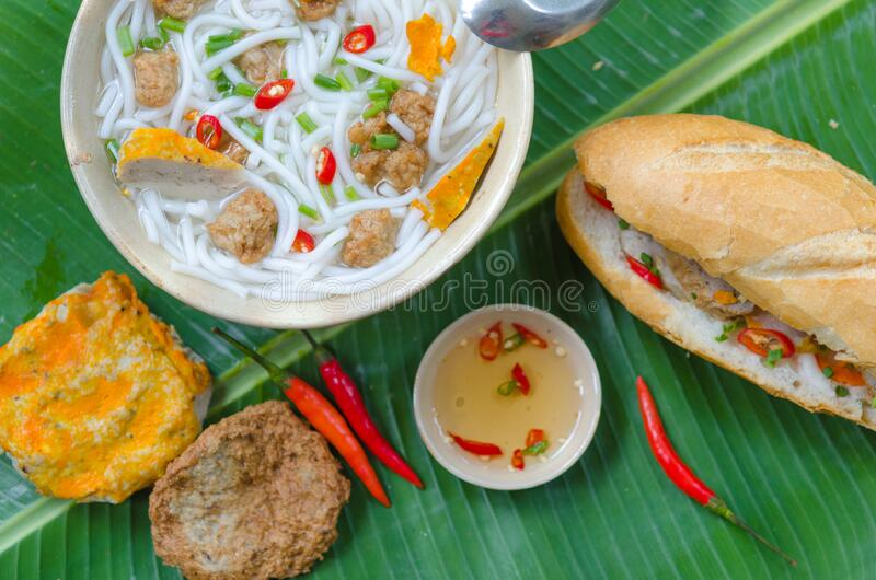 Banh Canh - Rice noodles soup with fried fish ball and Banh Mi Cha Ca - Vietnamese bread with fried fish and chili fish sauce. Inside. This is a typical combo stock images