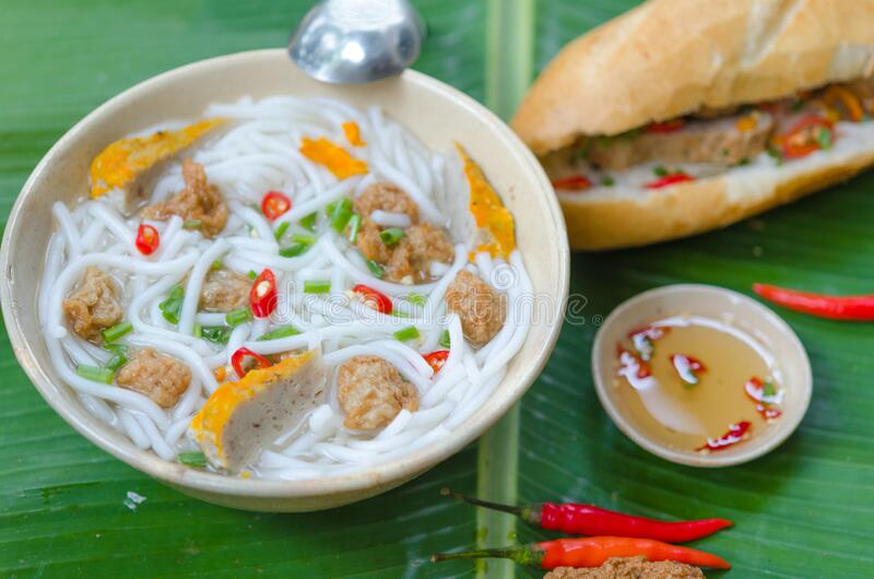 Banh Canh - Rice noodles soup with fried fish ball and Banh Mi Cha Ca - Vietnamese bread with fried fish and chili fish sauce. Inside. This is a typical combo stock image