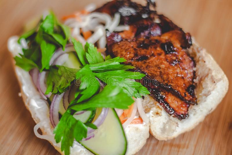 Banh Mi Vietnamese sandwich with pickled carrots asian radish ham and pate making process. All filling visible wooden background royalty free stock photography