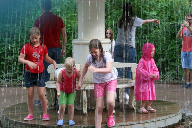 Banhando crianças sob a água da fonte imagens de stock