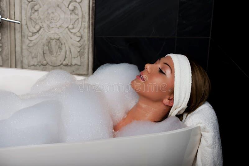 Banhando a mulher que relaxa no banho fotografia de stock