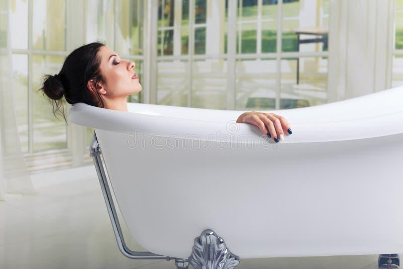 Banhando a mulher que relaxa no relaxamento de sorriso do banho com os olhos fechados foto de stock