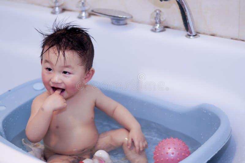 Banhando o bebé foto de stock