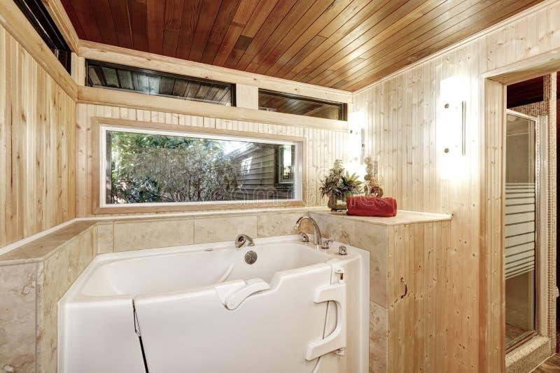 Banheira branca no banheiro almofadado de madeira imagem de stock