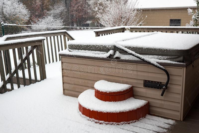 Banheira de hidromassagem coberta em um patamar residencial em uma tempestade da neve imagens de stock royalty free