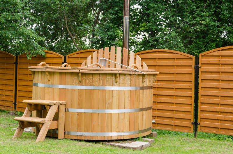 Banheira de hidromassagem de madeira moderna da água com as escadas exteriores fotografia de stock