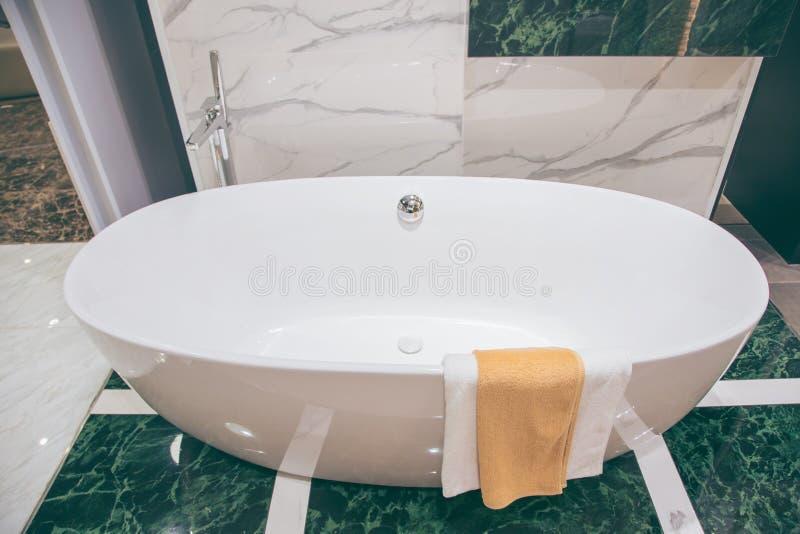 Banheira vazia do vintage luxuoso bonito perto da janela grande no interio do banheiro, espaço livre imagens de stock royalty free