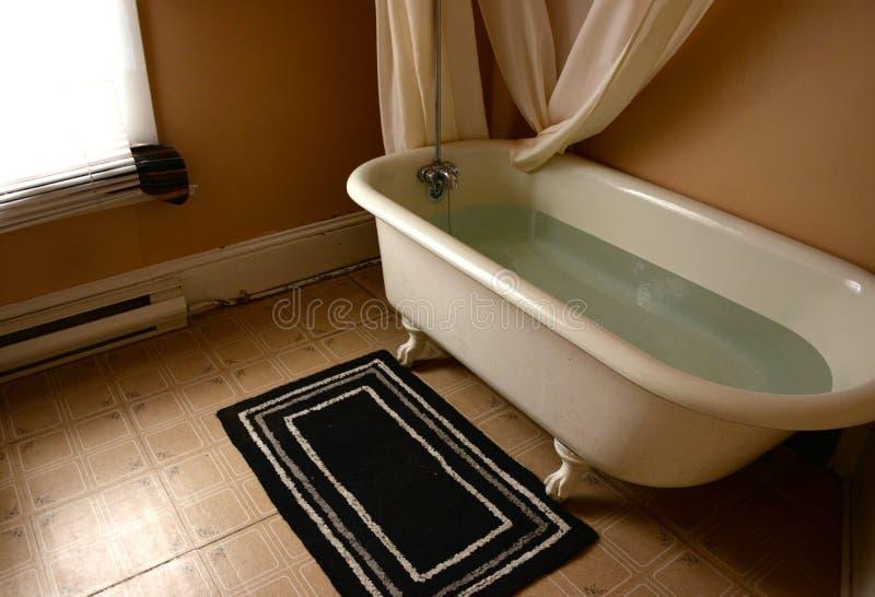 Banheira velha do pé da garra no banheiro velho fotografia de stock