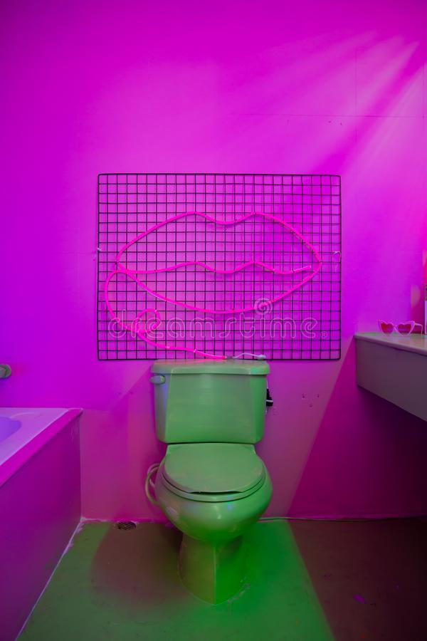 Banheiro abandonado no conceito das luzes de néon no estúdio imagens de stock