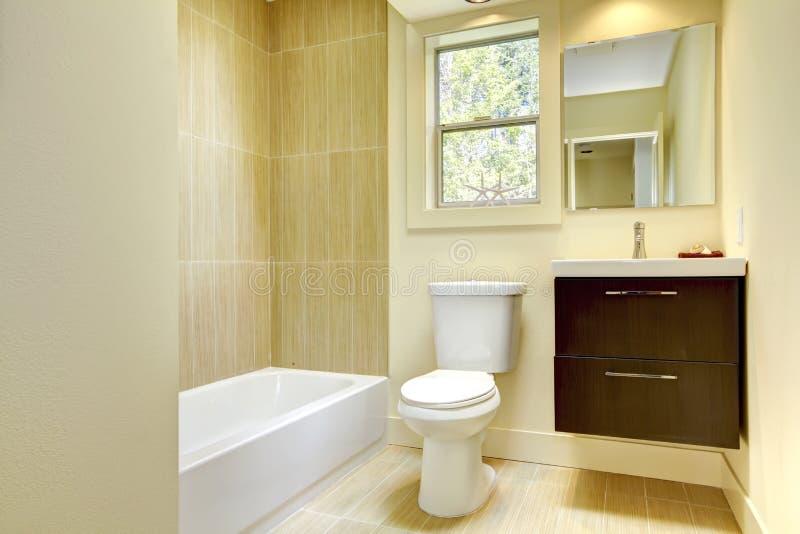 Banheiro amarelo moderno novo com telhas bege. fotografia de stock