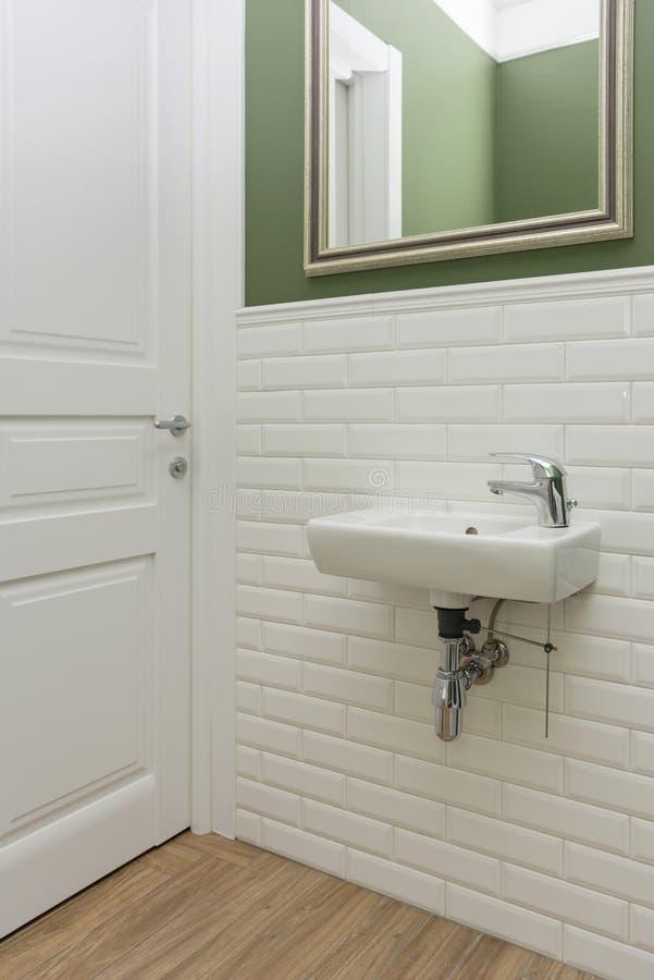 Banheiro, close-up do interior da sala do toalete As paredes são pintadas verdes, coberto com os azulejos decorativos com o bric  imagens de stock royalty free