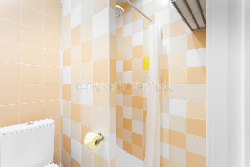 Banheiro com chuveiro, bacia de toalete e dissipador Quarto do padrão do hotel interior simples e à moda Iluminação interior imagens de stock