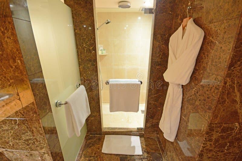 Banheiro com chuveiro luxuosa com toalhas e as vestes de banho brancas imagens de stock