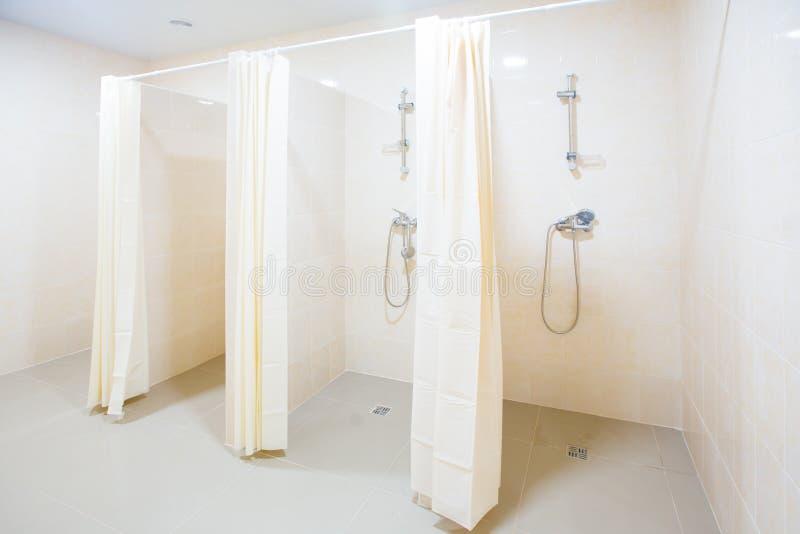 Banheiro com chuveiro pública com diversos chuveiros Banheiro com chuveiro pública grande, clara, vazia, com paredes brilhantes e fotografia de stock
