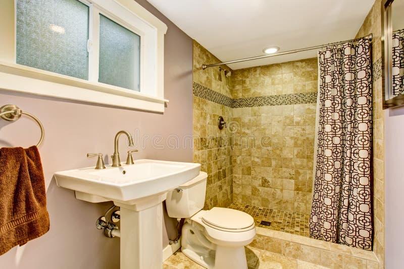 Banheiro com paredes roxas, o chuveiro verde e as cortinas agradáveis fotografia de stock