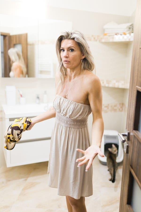 Banheiro de limpeza infeliz da mulher após a sujeira do gato imagem de stock royalty free