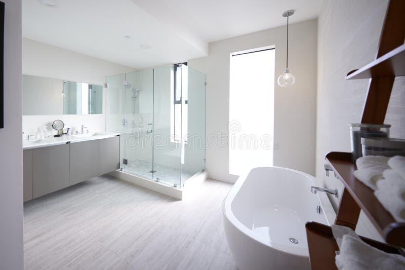 Banheiro doméstico moderno com cabine do chuveiro e banho autônomo, luz solar, nenhum pessoa foto de stock royalty free