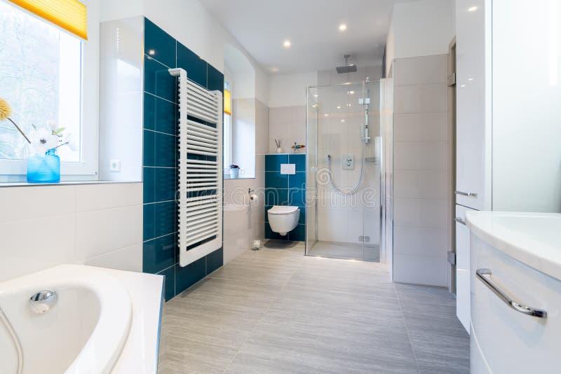 Banheiro espaçoso em tons azuis e brancos com assoalhos calorosos, chuveiro das pessoas sem marcação, vaidade do dissipador e cla fotos de stock