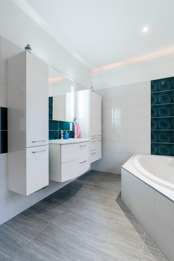 Banheiro espaçoso em tons azuis e brancos com assoalhos calorosos, chuveiro das pessoas sem marcação, vaidade do dissipador e tir fotos de stock royalty free