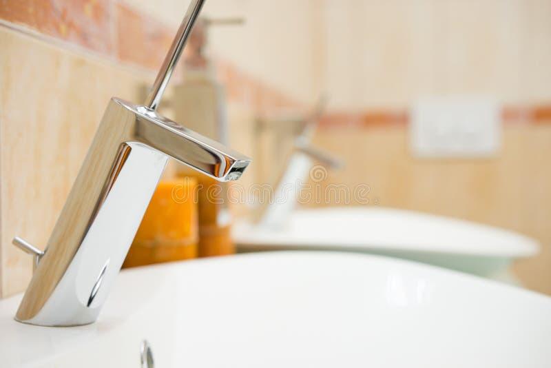 Banheiro moderno com dissipador e torneira, fundo borrado imagens de stock