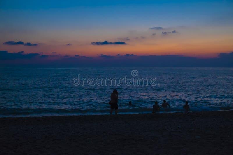 Banhistas em uma praia do mar após o por do sol fotografia de stock royalty free
