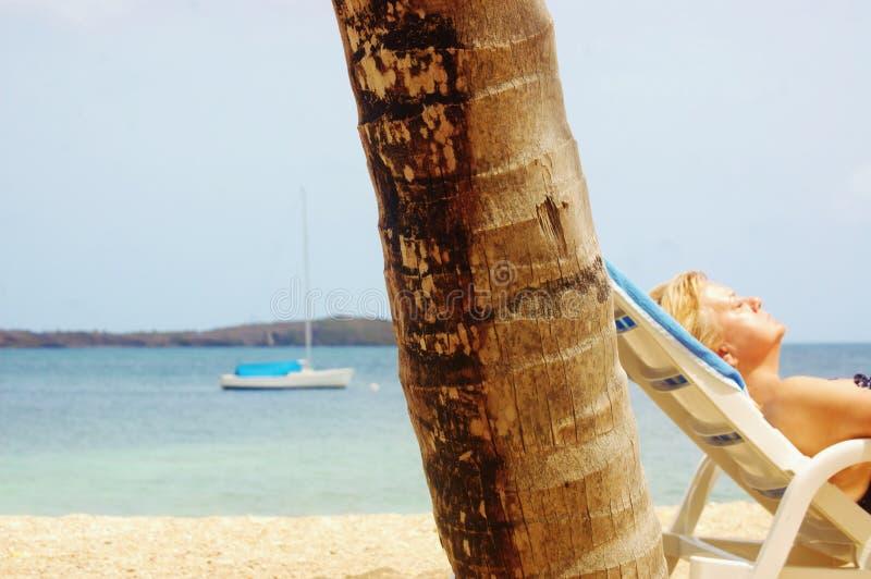 Banho de sol aposentado da mulher na praia imagem de stock