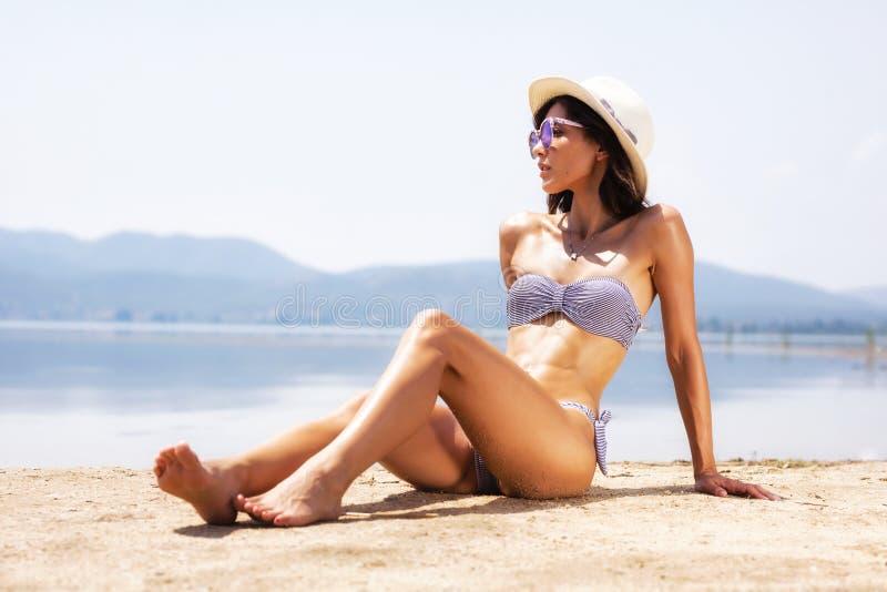Banho de sol bonito da menina em uma praia foto de stock