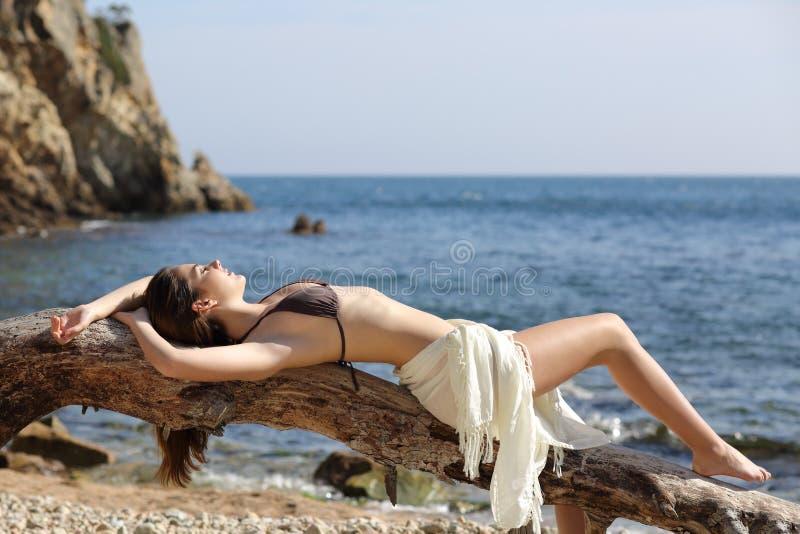 Banho de sol bonito da mulher na praia em férias imagens de stock