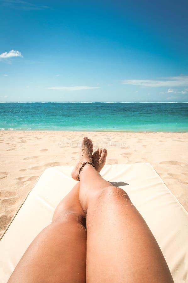 Banho de sol da jovem mulher na praia fotos de stock