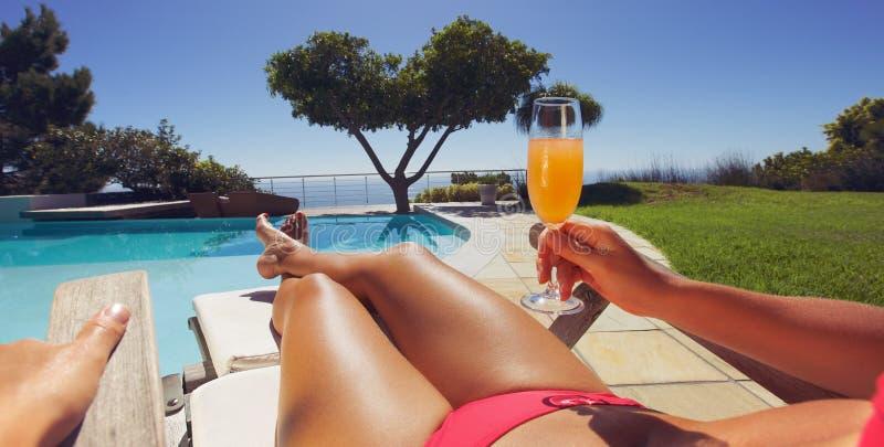 Banho de sol da mulher ao longo de uma associação com suco de laranja foto de stock