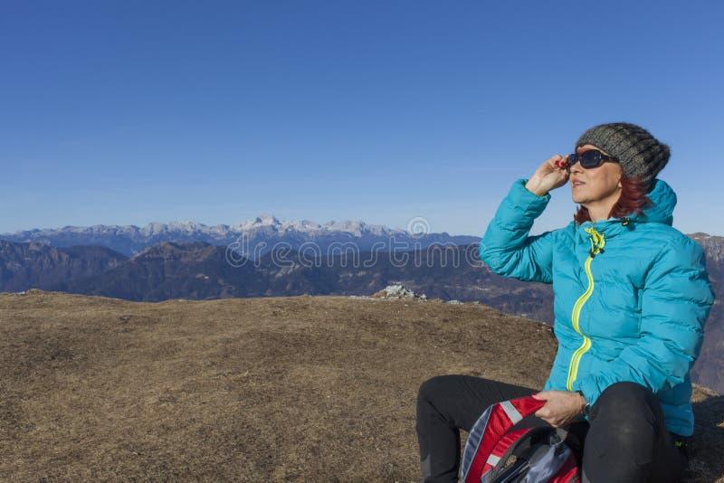 Banho de sol do trekker da mulher nas montanhas imagens de stock royalty free