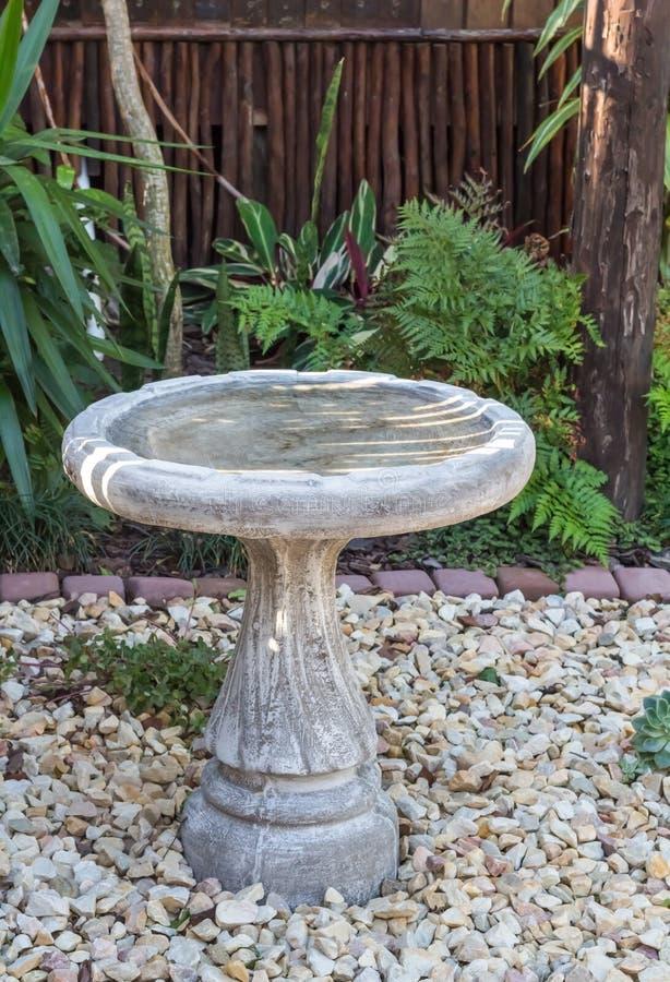 Banho do pássaro fora no cascalho da rocha no jardim projetado foto de stock